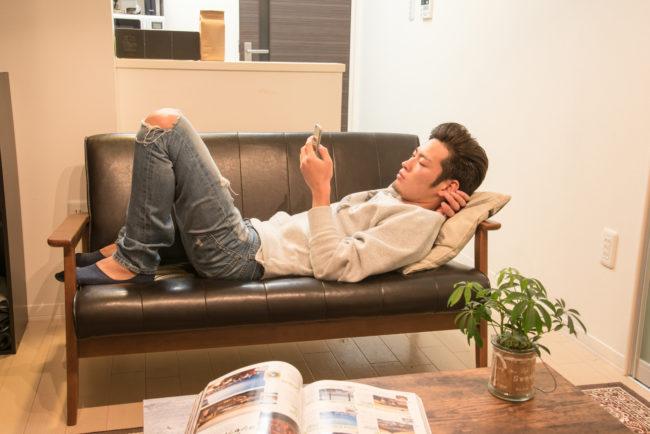 ソファで寝ながらスマホをいじる男性の画像